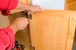 Closeup of a installers hands attaching a hinge a kitchen cabine