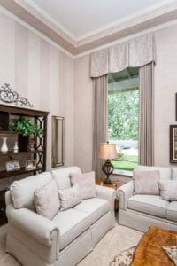 Custom drapes and top treatment add softness and color to this living room, while offering privacy.